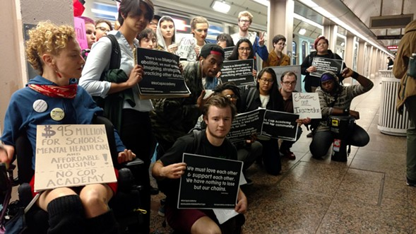 Activists pose for a photo before a train takeover for the #NoCopAcademy campaign - MAYA DUKMASOVA