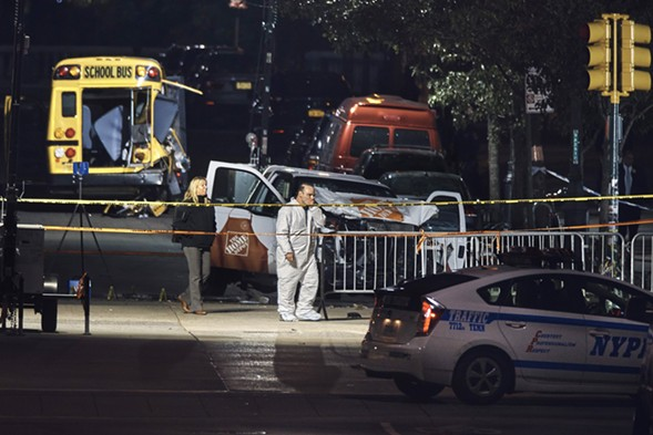Police work near a damaged Home Depot truck after a motorist drove onto a bike path near the World Trade Center memorial, striking and killing several people. - AP PHOTO/ANDRES KUDACKI