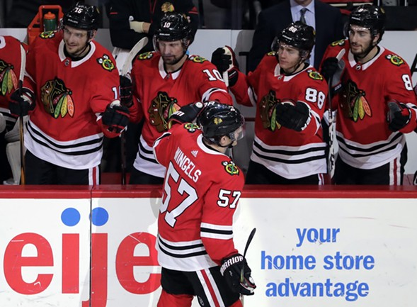 Chicago Blackhawks right wing Tommy Wingels (57) celebrates with teammates after scoring a goal. - AP PHOTO/NAM Y. HUH