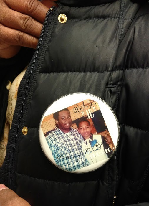 Tiffaney Boxley wears a pin with a photo of her son - BEAL FAMILY PHOTO