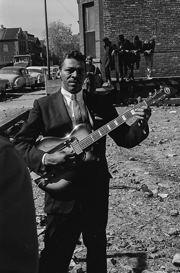 Little Walter poses with his guitar near Maxwell Street in the early 1960s after busking at the market earlier that day. - CHICAGO HISTORY MUSEUM