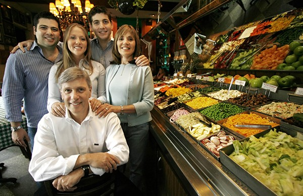 Richard Melman (front) poses by the salad bar in his first reataurant, R.J. Grunt's, in Chicago's Lincoln Park neighborhood with his family. - SPENCER GREEN