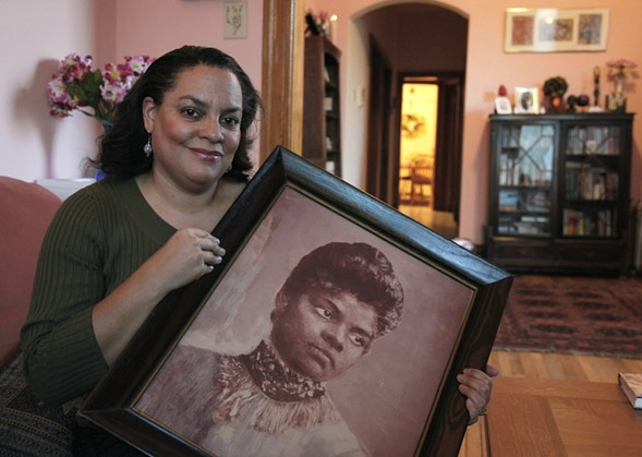 Michelle Duster in her Chicago home with a portrait of her great-grandmother Ida B. Wells-Barnett - AP/CHARLES REX ARBOGAST
