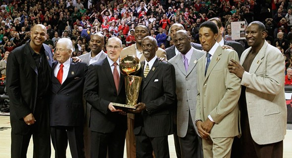 Members of the 1990-'91 Chicago Bulls celebrate the 20th anniversary of their championship season during halftime of a March 2011 game. Hodges, center, holds the trophy. - AP PHOTO/CHARLES REX ARBOGAST