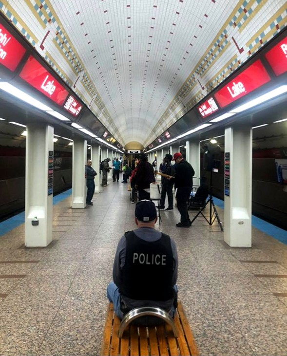 Johnston recently captured this photo of a police officer listening to a band perform at the Lake Red Line station—an unauthorized performance location. - ANDREW JOHNSTON