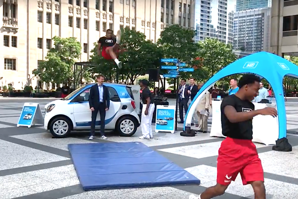 The Jesse White Tumblers jump over Car2go CEO Olivier Reppert's head at the launch. - JOHN GREENFIELD