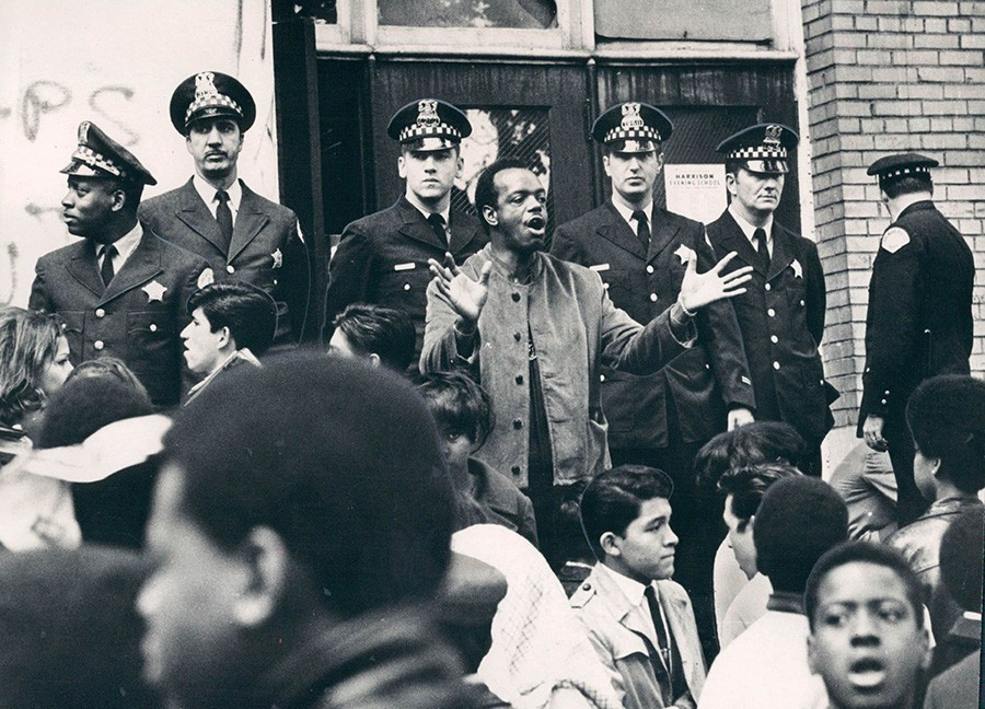 A city youth welfare street worker pleads with students to go home after a walkout at Harrison High school on October 9, 1968. Police line the school entrance. - LARRY GRAFF