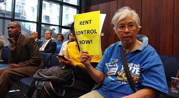 A member of the Jane Addams Senior Caucus listens to state senate testimony about a bill that would enact rent regulation in Illinois - MAYA DUKMASOVA