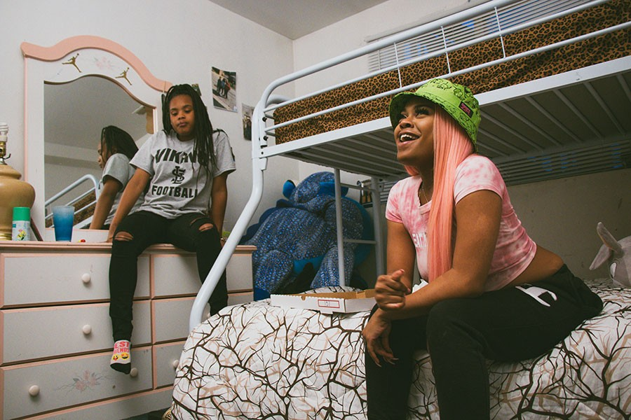 Queen Key on the bottom bunk in her cousins' bedroom in Blue Island, where she used to write her songs. Her 15-year-old cousin Aniya is to the left. - QURISSY LOPEZ