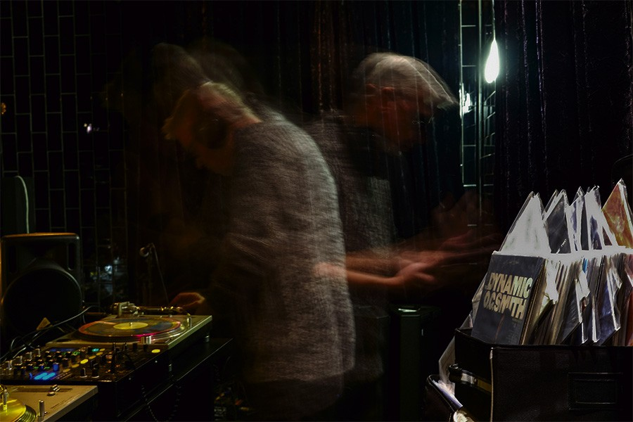 Dorian's programming director Joe Bryl spins records on the small stage behind the bar. - PINAR ISTEK