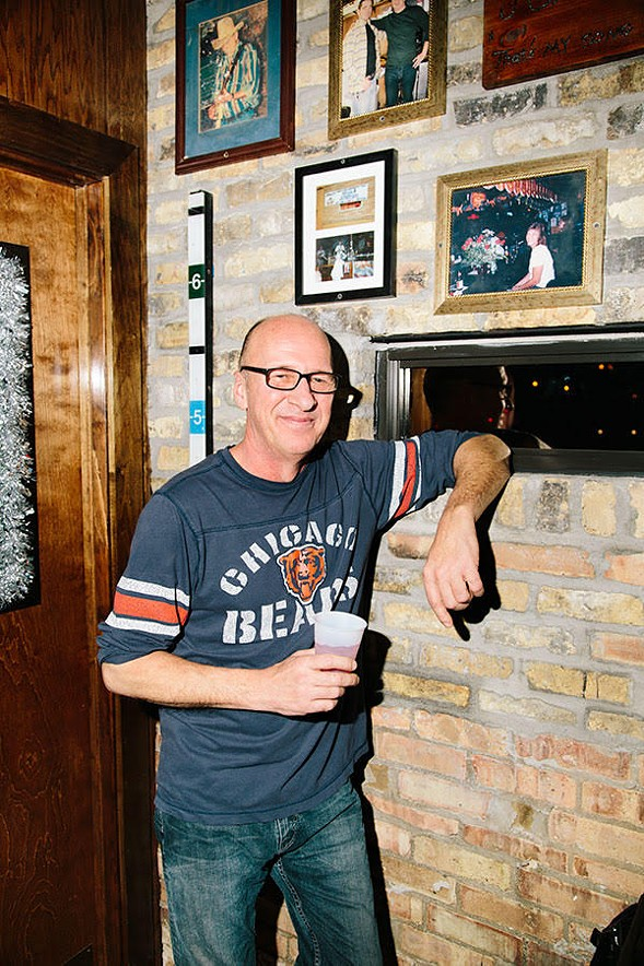 Bob Hirtzig, brother of former Carol's owner Carol Harris, poses with a photo of Harris at the bar (above his left elbow). - MATTHEW SCHWERIN