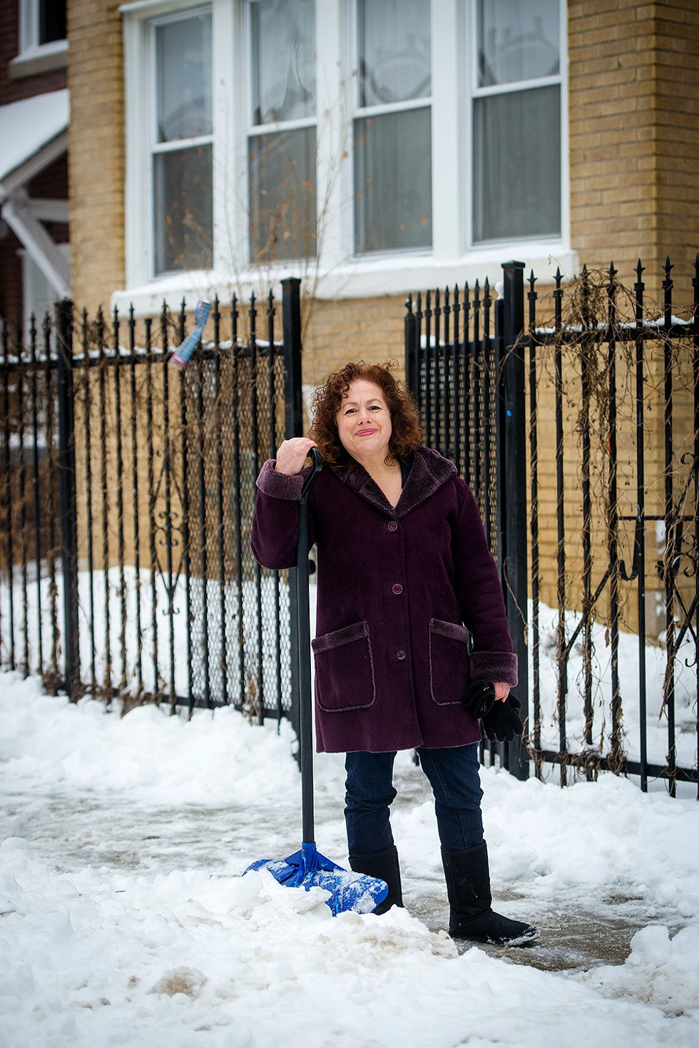 """Cherie Travis stands outside of one of her properties near Logan Square. She's against lifting the ban on rent control. """"It is already a treacherous place for small landlords in Chicago,"""" she says. """"[Rent control] creates a massive disincentive for landlords to keep up the property."""" - KATHLEEN HINKEL"""