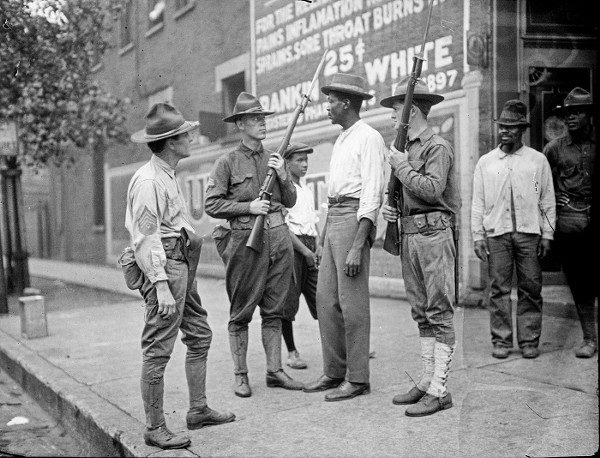 Armed National Guard and African American men stand on a sidewalk during the race riots in Chicago in 1919. - JUN FUJITA | COURTESY CHICAGO HISTORY MUSEUM