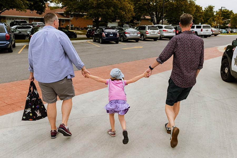 Tanner (left) and Colville (right) hold hands with their daughter, Morgan Tanner, on their way to Skokie Pride - RYAN EDMUND
