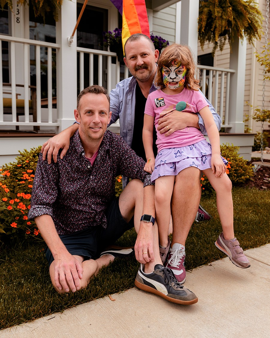 Husbands Justin Colville (left) and Nate Tanner (right) with daughter Morgan Tanner in front of their Skokie home. The husbands adopted Morgan in an open arrangement through the Cradle in Evanston. - RYAN EDMUND