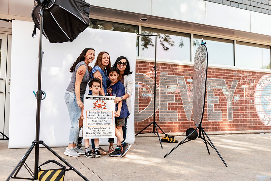 Volpe and Santos posing for a photograph with their three children at an anti-racism demonstration at Dewey Elementary School in Evanston - RYAN EDMUND