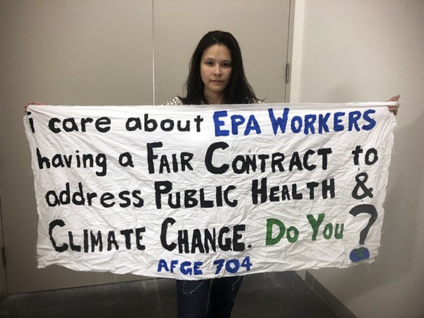 EPA project officer Loreen Targos and the banner she unfurled in protest - NICOLE CANTELLO