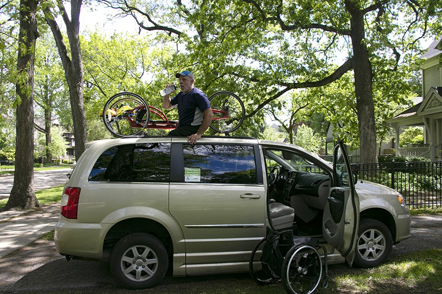 Lenzo puts his handcycle onto the van in his yard in Oak Park. - CAROLYN CHEN