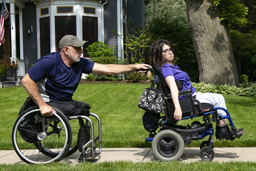 Lenzo wheels with Cynthia outside their house in Oak Park. Cynthia's cerebral palsy makes it difficult for her to move and maintain balance. - CAROLYN CHEN