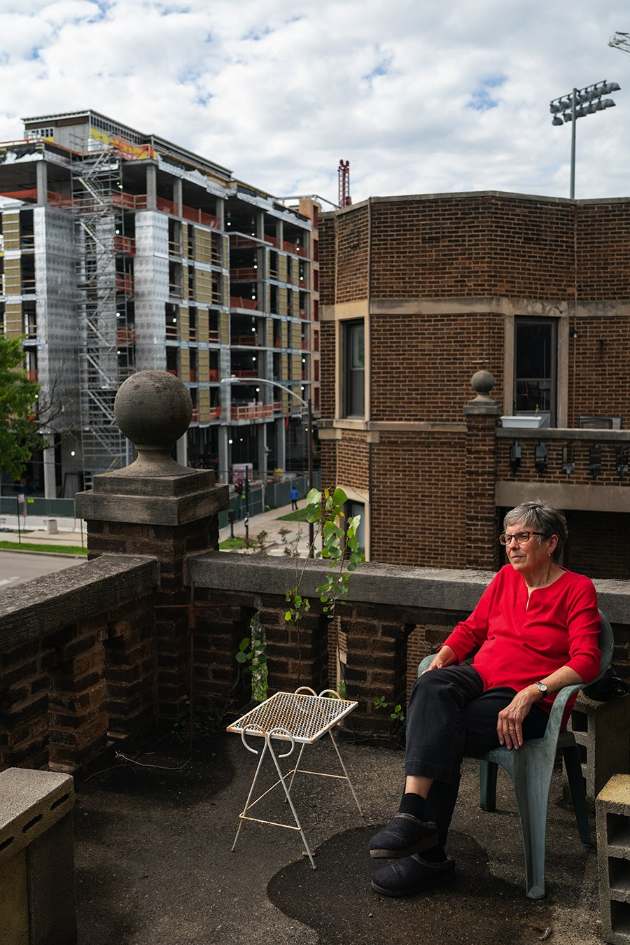 Sara Pitcher sits on the balcony of her co-op apartment on Woodlawn Avenue and 61st Street with University of Chicago construction dominating her view to the north. Pitcher is the last original resident of these apartments rehabbed and co-founded by her late husband, Rev. Al. Pitcher, and the Covenant Community of University Church over 40 years ago. - MAX HERMAN