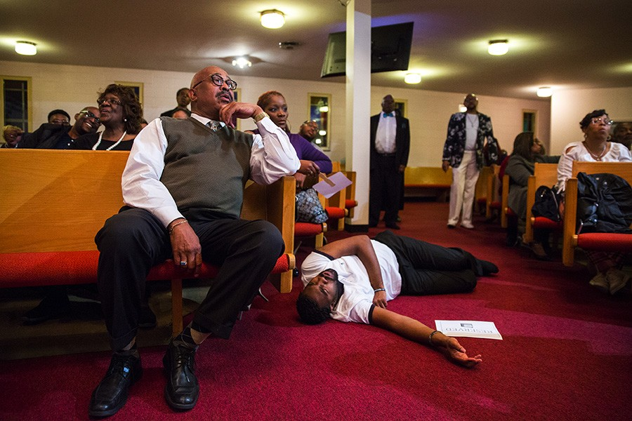 A congregant lies on the floor after feeling the spirit during a Mama Lou choir performance at Greater New Mount Moriah Missionary Baptist Church in Detroit. - GEOFF STELLFOX FOR CHICAGO READER