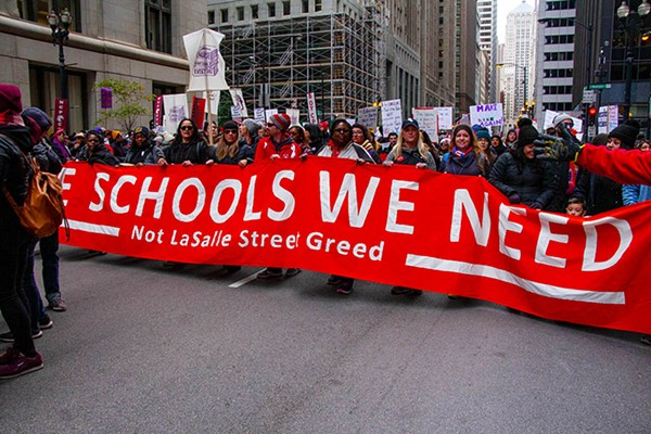Striking Chicago teachers march through downtown on October 17. - CHARLES EDWARD MILLER