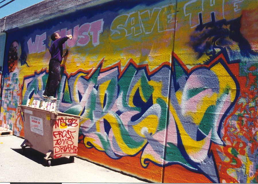 """Roberts paints """"We Must Save the Children"""" on a retaining wall near the Berwyn Red Line stop in 1995 as part of a citywide CTA project. - COURTESY DARRELL """"ARTISTIC"""" ROBERTS"""