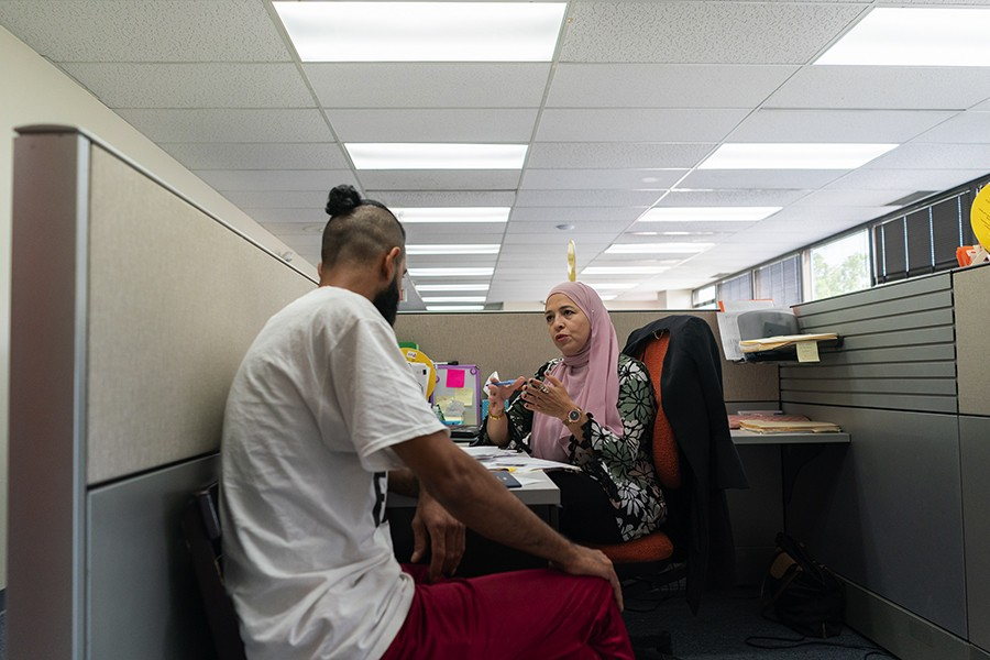 Fouzia Othman works with a client at the Arab American Family Services office. Case managers help community members with translating mail, applying for WIC and SNAP benefits, immigration paperwork, and other needs. - MAX HERMAN