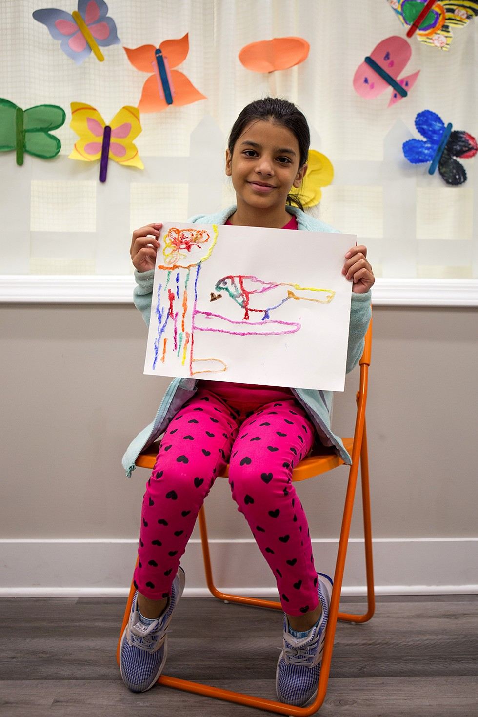 Nour, 9, presents a bird she drew using salt and watercolors. She and her family also moved to Chicago from Syria about three years ago. - FARAH SALEM FOR CHICAGO READER