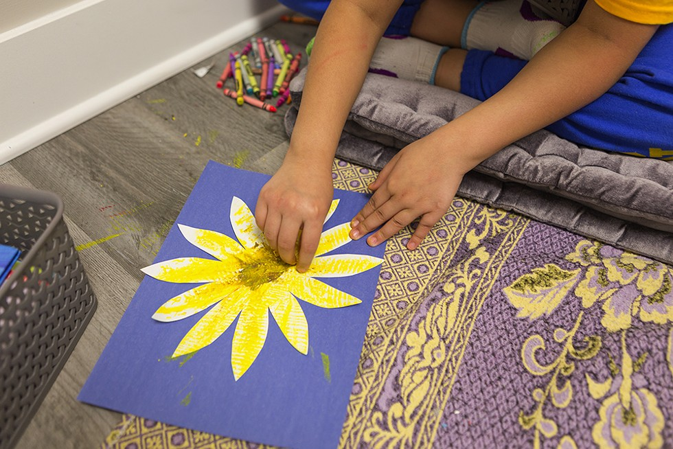An eight-year-old participant colors jasmine flower cutouts. - FARAH SALEM FOR CHICAGO READER