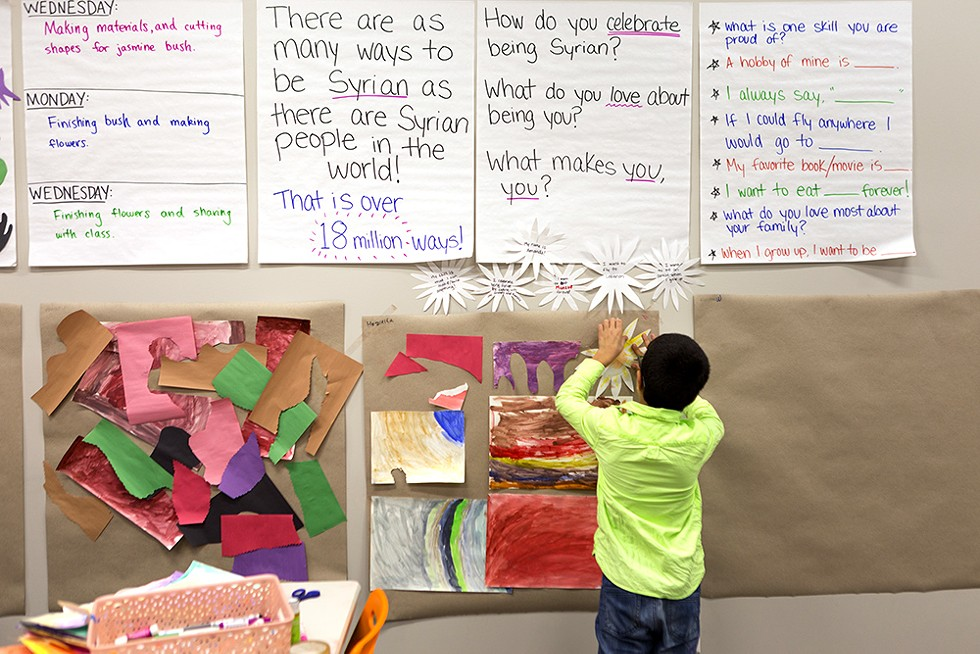 Hozaifa, 7, hangs watercolor drawings and jasmine leaf cutouts he created at the Syrian Community Network's afterschool program. - FARAH SALEM FOR CHICAGO READER