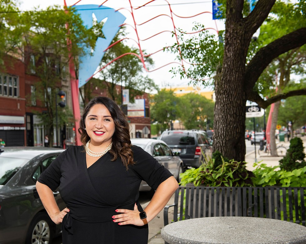 Illinois state rep. Delia Ramirez stands in front of a Puerto Rican flag in Humboldt Park. - AZADEH KHASTOO