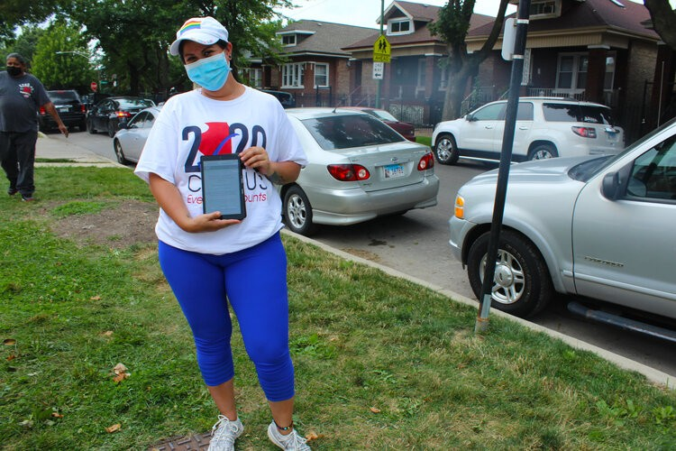 Maribel Sanchez, a volunteer with the Brighton Park Neighborhood Council, volunteered at a food distribution site before approaching people in line to count them in the census. - ALEXANDRA ARRIAGA