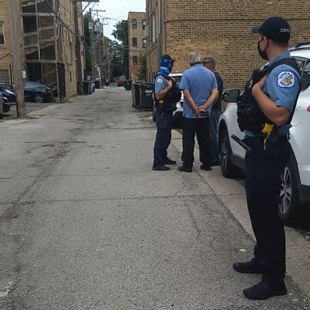 CPD officer Joshua Surgal (with the blue neckwarmer on his face) spoke with the men who extracted a tenant at gunpoint out of earshot of bystanders. - MAYA DUKMASOVA