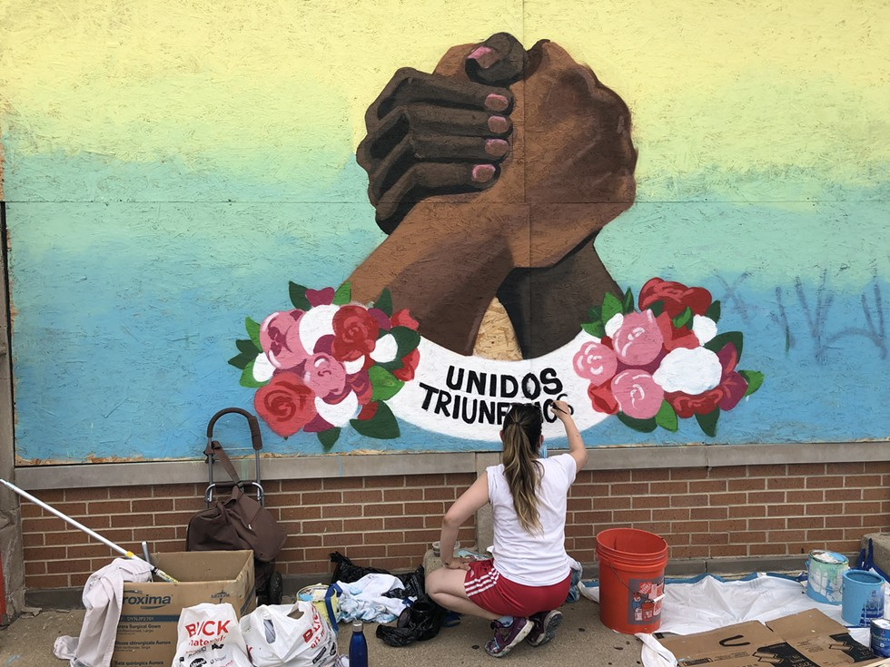 Veronica Martinez working on her third mural for Alivio Medical Center in Little Village. - EMILY BOYCE