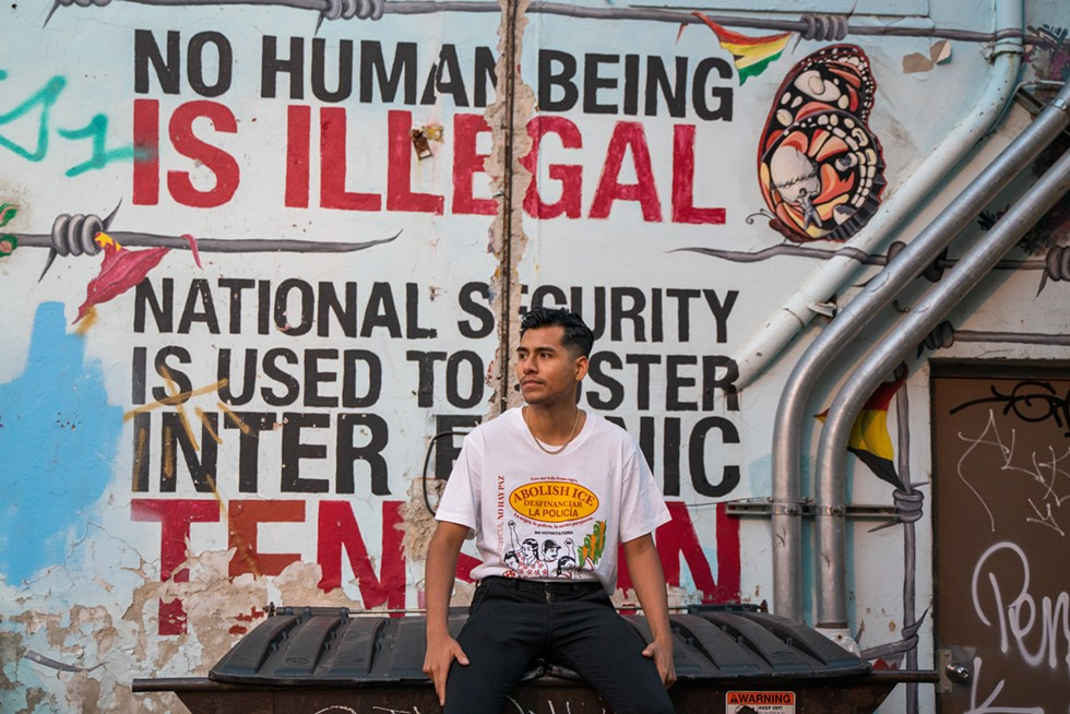 Fernando Delgado wears his T-shirt in front of a mural celebrating immigrants in Pilsen. - OSCAR SANCHEZ