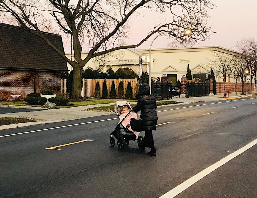 A woman pushes a stroller to Congregation Shaarei Tzedek Mishkan Yair in West Rogers Park at Sundown on a Friday evening. Without the eruv, using the pram would violate Sabbath rules. - JOHN GREENFIELD