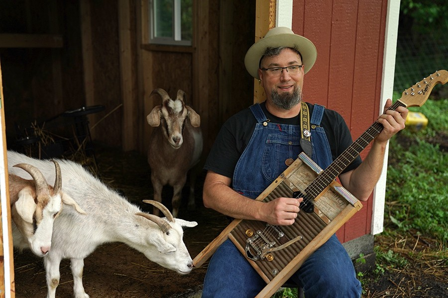 A goat takes an interest in Leise's washboard guitar. - ELIZABETH SISSON