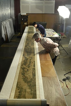 Museum workers prepare the Qingming scroll painting for display.
