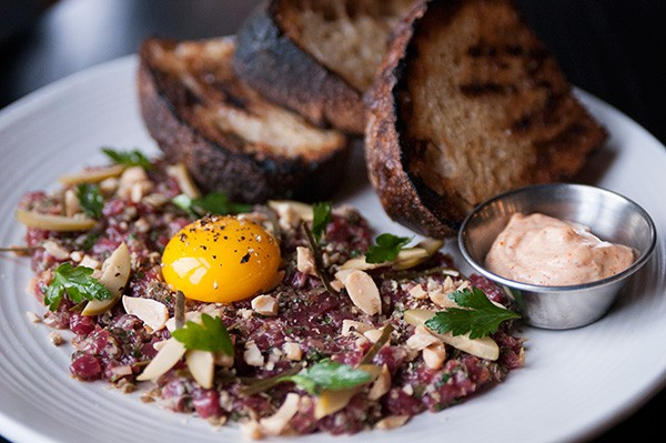 The mineral gaminess and textural oleaginousness of lamb tartare and its accompanying protein-rich raw egg yolk is cut with chopped almonds, caper leaves, and potent harissa aioli.