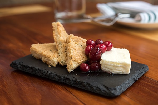 A dessert features an Italian cheese called Il Nocciolo served with triangles of rigid, rosemary-scented shortbread and a dollop of sweet cranberry jelly.
