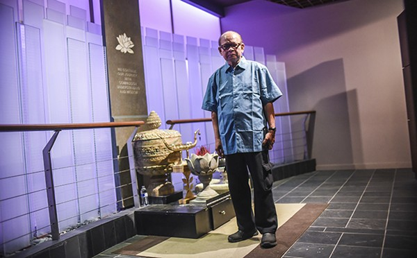 Kompha Seth stands in front of the Killing Fields Memorial at the Cambodian Association of Illinois's National Cambodian Heritage Museum.