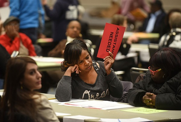 Vonettia Midgett, of Detroit, awaits assistance as the massive recount begins in Wayne County, Michigan, Tuesday.