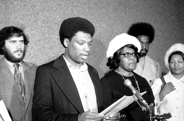 Bill Hampton, brother of Fred Hampton, reads a statement during a 1974 press conference with, to his right, family members of slain Panther Mark Clark.