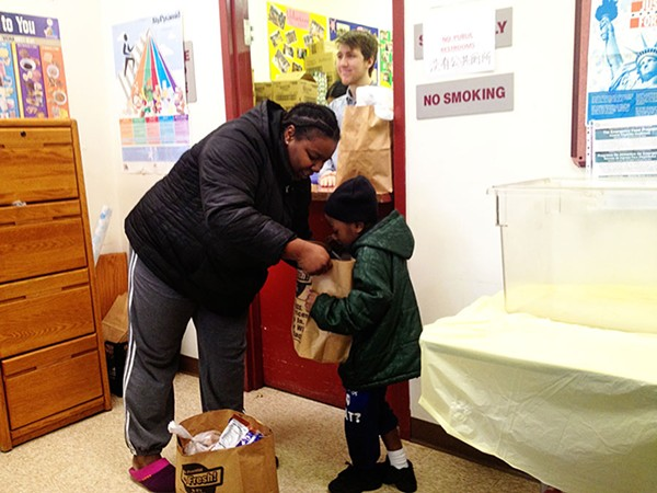 Dominique Huntley, 26, and her four-year-old son Tyler at Saint James Food Pantry at 29th and Wabash. Under the Trump administration's plan, food stamp recipients would receive boxes of shelf-stable food.