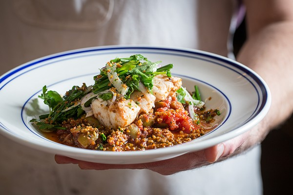 Hake with tomato sauce, green olives, and ground and crisped serrano ham