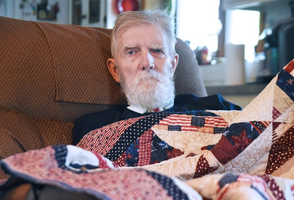 George Holtz poses for a portrait with his Quilt of Valor in his Bloomingdale, Illinois, home on June 1, 2019.