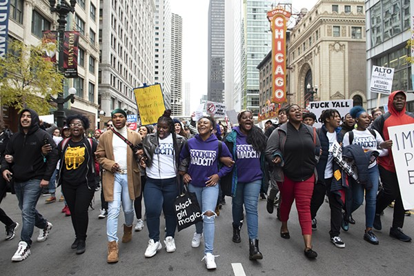 Protesters march down State Street, past the Chicago Theater.