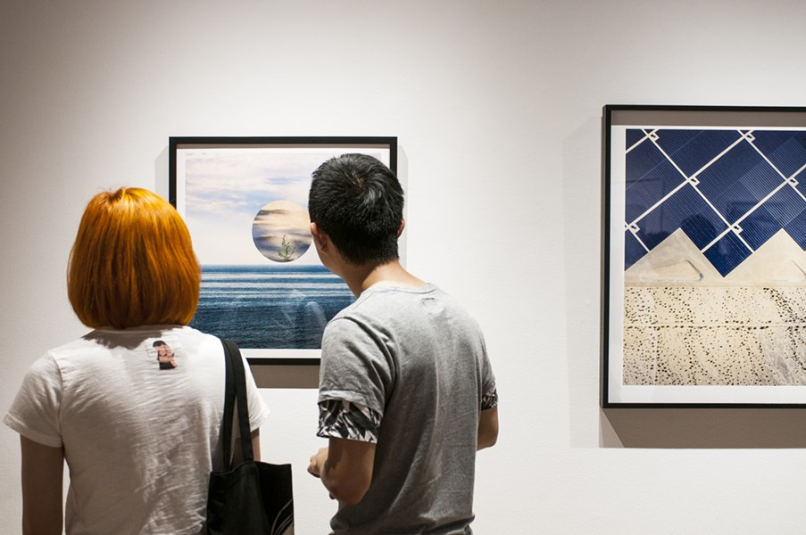 "Art goers view an image in the ecologically themed exhibit ""Field Study."" - ANDREA BAUER"