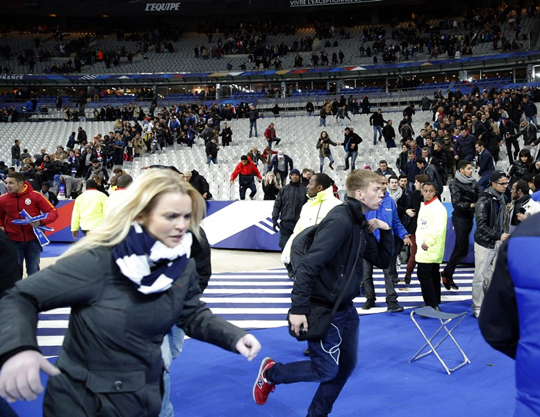 Hundreds of people spilled onto the field of the Stade de France stadium after explosions were heard nearby during a match between the French and German national soccer teams. - AP PHOTO/CHRISTOPHE ENA